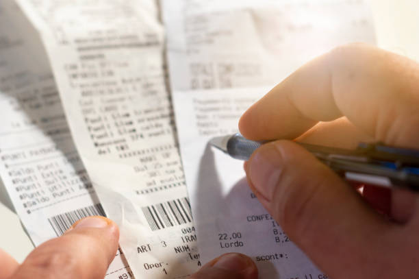 checking a receipt by analyzing the numbers, expenses and profits. - scontrino foto e immagini stock