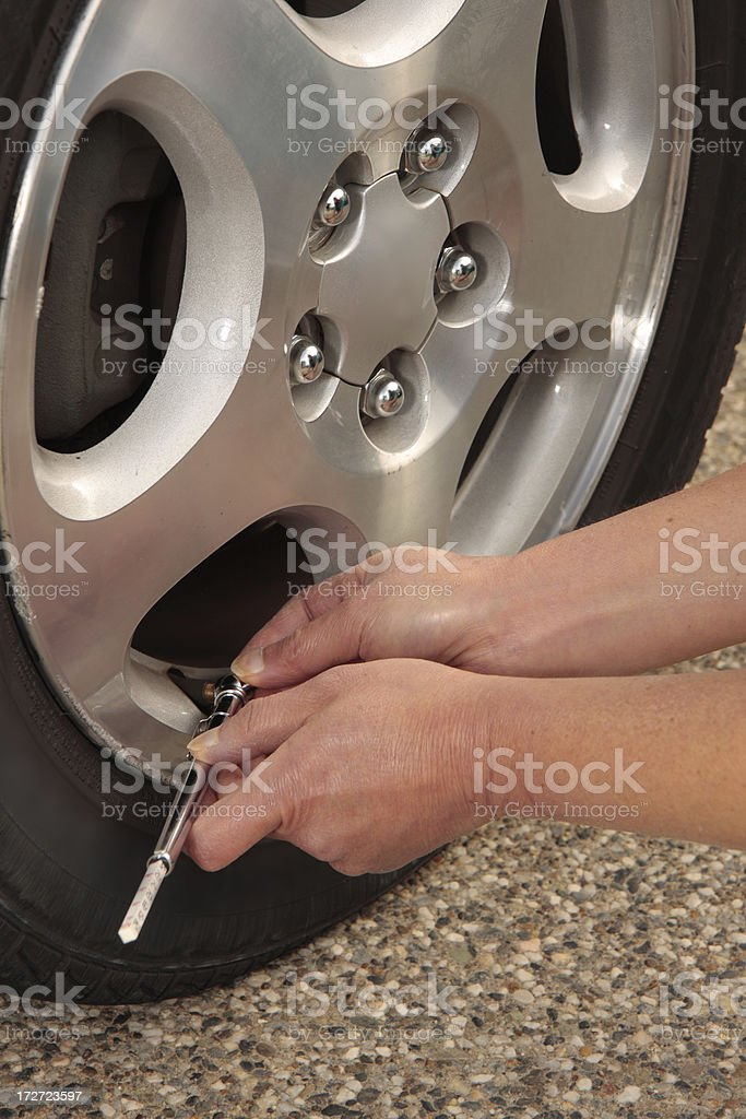 Checking a tire's air pressure (vertical) royalty-free stock photo