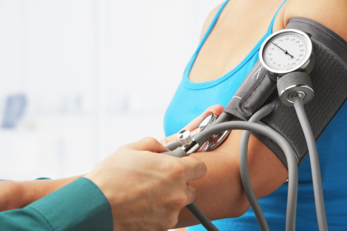 Checking Blood Pressure Of Female Patient Stock Photo - Download Image Now