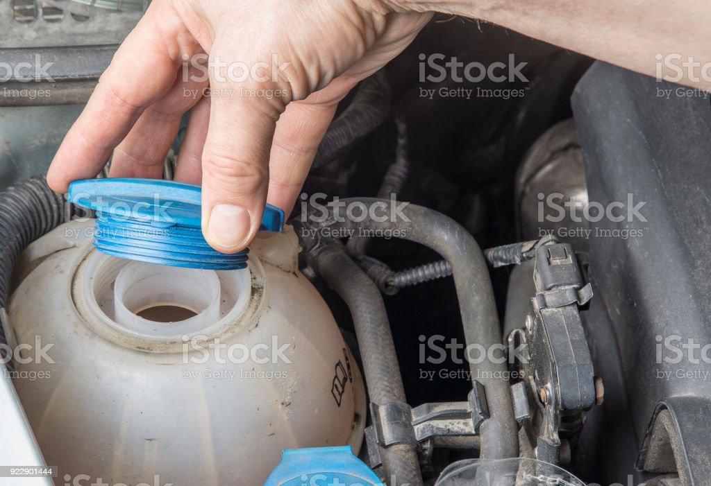 Checking car radiator coolant level and add up liqiud. stock photo
