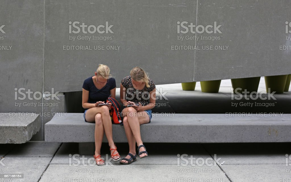 Checking Devices at Nathan Phillips Square, Toronto, Canada in Summer stock photo