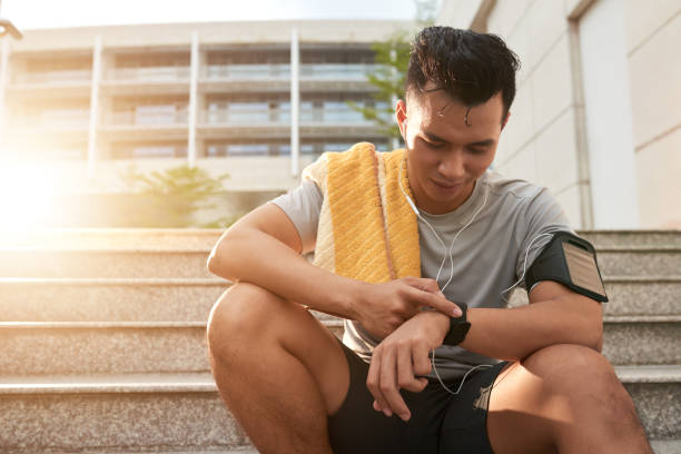 Checking fitness tracker Young Vietnamese man checking smartwatch after jogging in the morning fitness tracker stock pictures, royalty-free photos & images