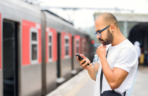 Checking for the next train online stock photo