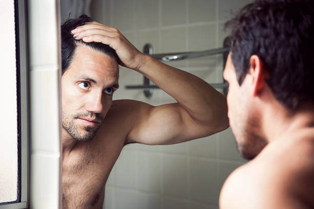 Checking Hairline Man checking hair in mirror. human scalp stock pictures, royalty-free photos & images
