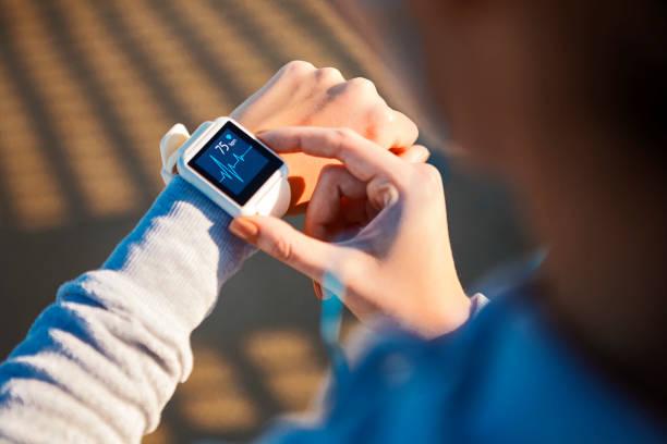 checking her heart rate on a smart watch - attrezzatura per esercizi foto e immagini stock