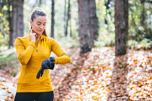 Checking Her Heart Rate Woman doing exercises outdoors woman taking pulse stock pictures, royalty-free photos & images