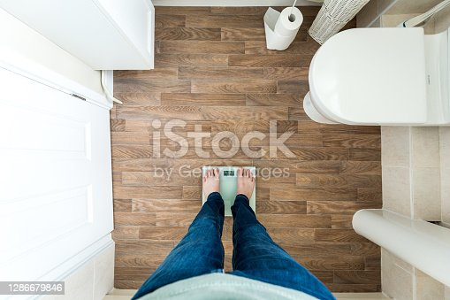 Wide angle color image depicting a man standing on electronic weighing scales, checking his weight in the bathroom at home. Room for copy space.