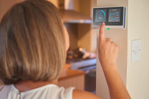 Checking home energy consumption Homeowner checking current energy costs on smart meter in the kitchen of her home smart thermostat stock pictures, royalty-free photos & images