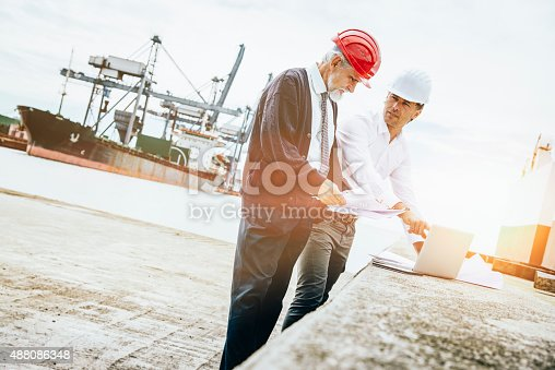 Inspectors at the commercial dock. They are looking at laptop computer and some papers. They are wearing protective helmets.