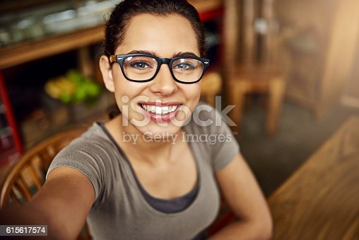 Shot of a young woman taking a selfie while sitting in a cafe