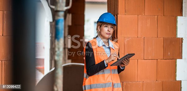 An architect using digital tablet to see if everything is going according to the plans