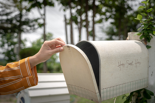 A hand of personal is opening the classical vintage style mailbox to check to letter inside. The mailbox is installed in front of the house, surrounded by garden environment.