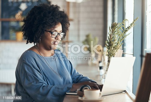 Shot of an attractive young businesswoman sitting and working on her laptop in a coffee shop during the day