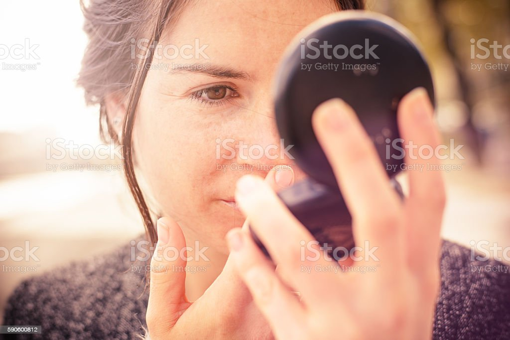 Checking my Look in Powder Compact Mirror royalty-free stock photo