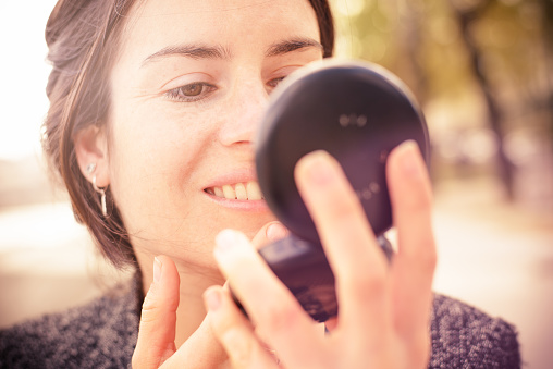 Young woman outdoors in Paris checking her face in a round powder compact mirror.