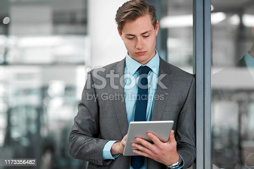 Cropped shot of a handsome young businessman standing alone in his office and using a tablet