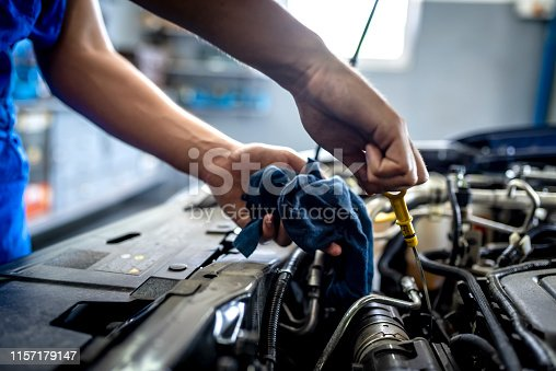 Photo of Unrecognizable male mechanic measuring the oil level of an engine at an auto shop. Mechanic checking the oil level in a car service garage. Repairing engine at a service station. Car repair.