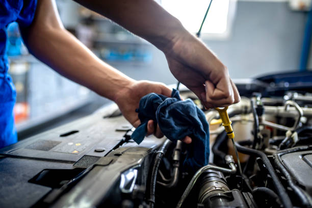 "Checking oil in car engine Photo of Unrecognizable male mechanic measuring the oil level of an engine at an auto shop. Mechanic checking the oil level in a car service garage. Repairing engine at a service station. Car repair.""r""n. mechanic stock pictures, royalty-free photos & images"