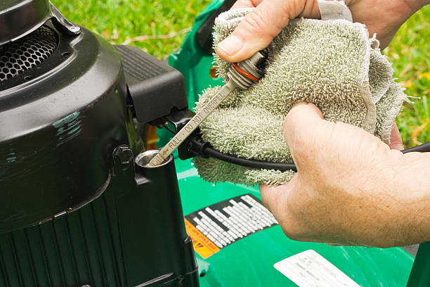 checking oil on a lawn mower stock photo