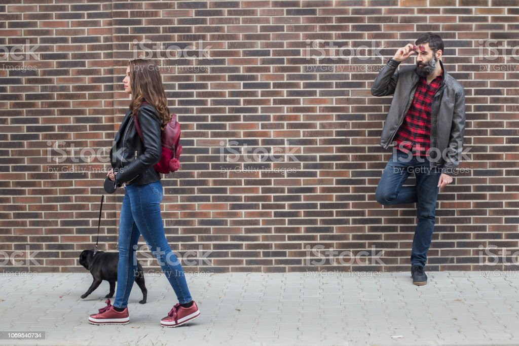 Checking out a young woman walking with a dog stock photo