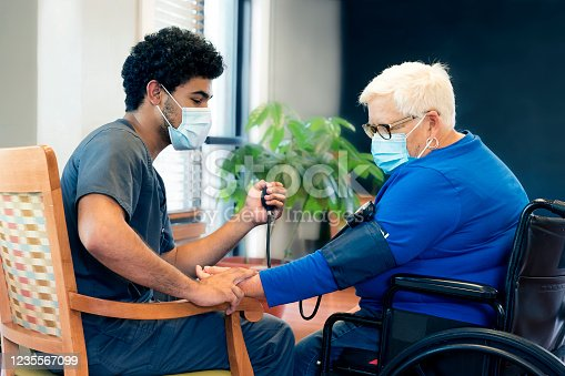Portrait of a smling African-American male nursing employee wearing gray scrubs and face mask interacts with a senior aged patient during the Covid-19 pandemic, Midwest, USA