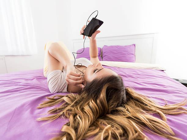 checking phone and listening to music - lila teenschlafzimmer stock-fotos und bilder
