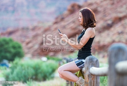 Profile view of a woman sitting on a fence while she checks her smartphone for messages.
