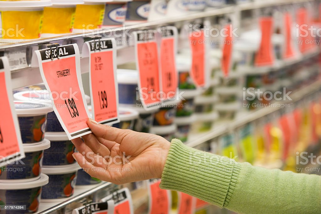 Checking price of item in supermarket aisle Lizenzfreies stock-foto