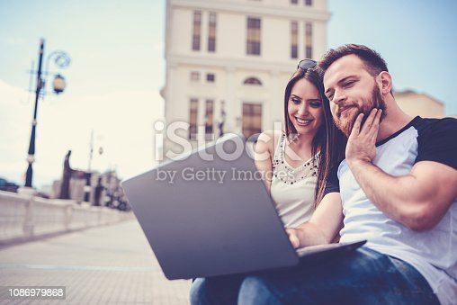 Cute Couple Checking For A Exam Results On Laptop  While Relaxing Outdoors