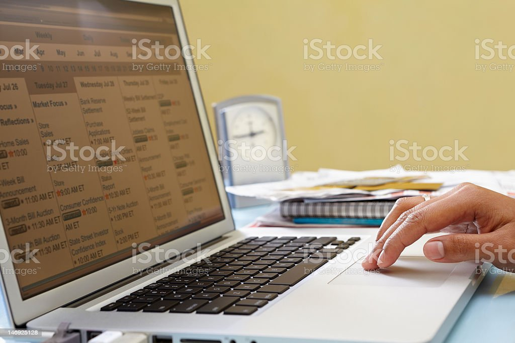 Checking schedule on laptop stock photo