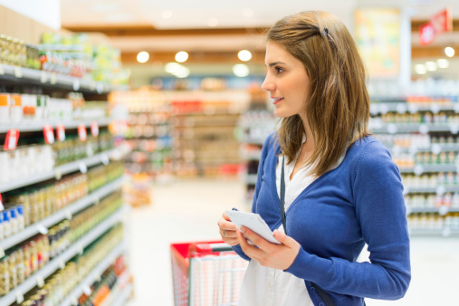 Young woman cheking shopping list in supermarket.