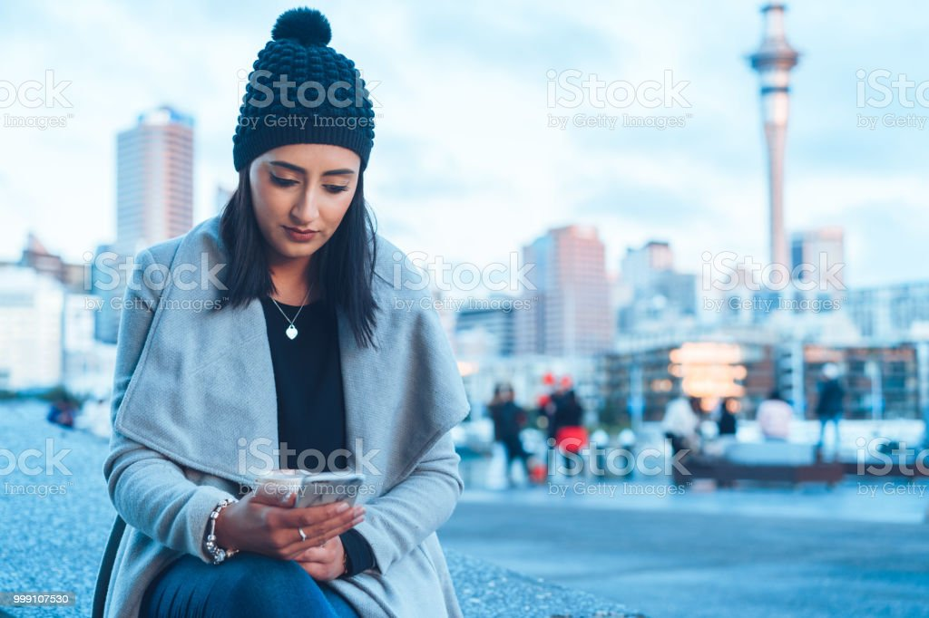 Checking social media on phone with Auckland city in background. stock photo
