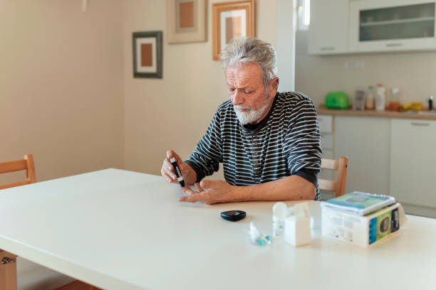 Checking sugar level Senior man with glucometer checking blood sugar level at home. Elderly man testing for high blood sugar. Man holding device for measuring blood sugar. medicine, age, diabetes, healthcare and old people concept lancet arch stock pictures, royalty-free photos & images