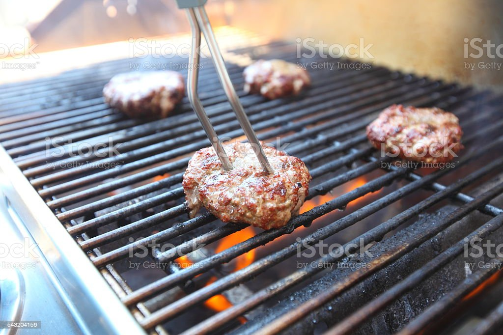 Checking temperature while grilling hamburgers stock photo