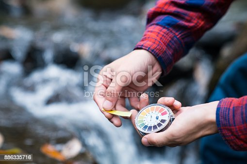 Checking the acidity and alkaline levels of river water with litmus paper