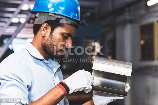 Young engineer checking the diameter of the metal plates being used for assembly