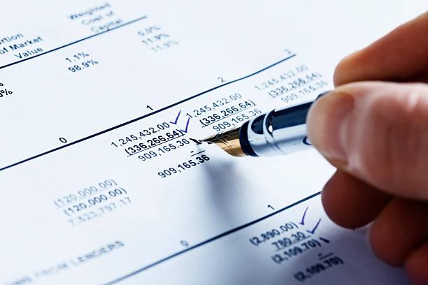 Verificar las finanzas; hombre mano señala la hoja de cálculo de datos - foto de stock
