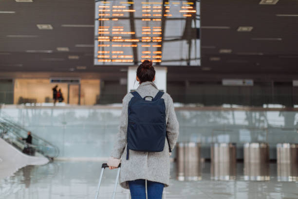 checking the flight schedule - arrival departure board stock photos and pictures
