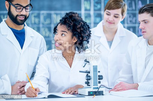 A diverse group of university students stands at a desk while recording results for their experiment. Most of the students are looking at the woman of african descent as she is the one writing.