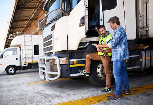 Shot of two coworkers talking together next to a large truck outside of a distribution center