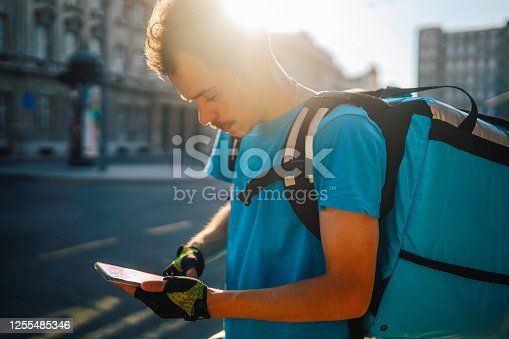 Image of a young food delivery man in downtown area. He is using a smartphone to pick up the next delivery.