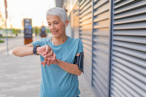 Checking the pulse. Mature Runner Checking Smart Watch. Checking Fitness Statistics On Smart Watch. Athletic mature woman monitoring her running performance on smartwatch woman taking pulse stock pictures, royalty-free photos & images