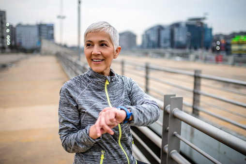 Mature woman using smart watch while work out