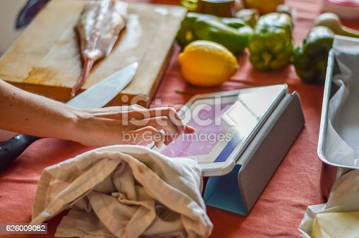 istock checking the recipe on tablet while cooking 626009082