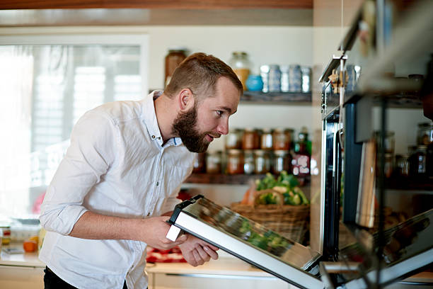 Checking to see if it's done Shot of a young man cooking at homehttp://195.154.178.81/DATA/i_collage/pu/shoots/805783.jpg bachelor stock pictures, royalty-free photos & images