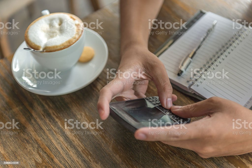 Checking to-do list on cellphone and having cappuccino in morning stock photo