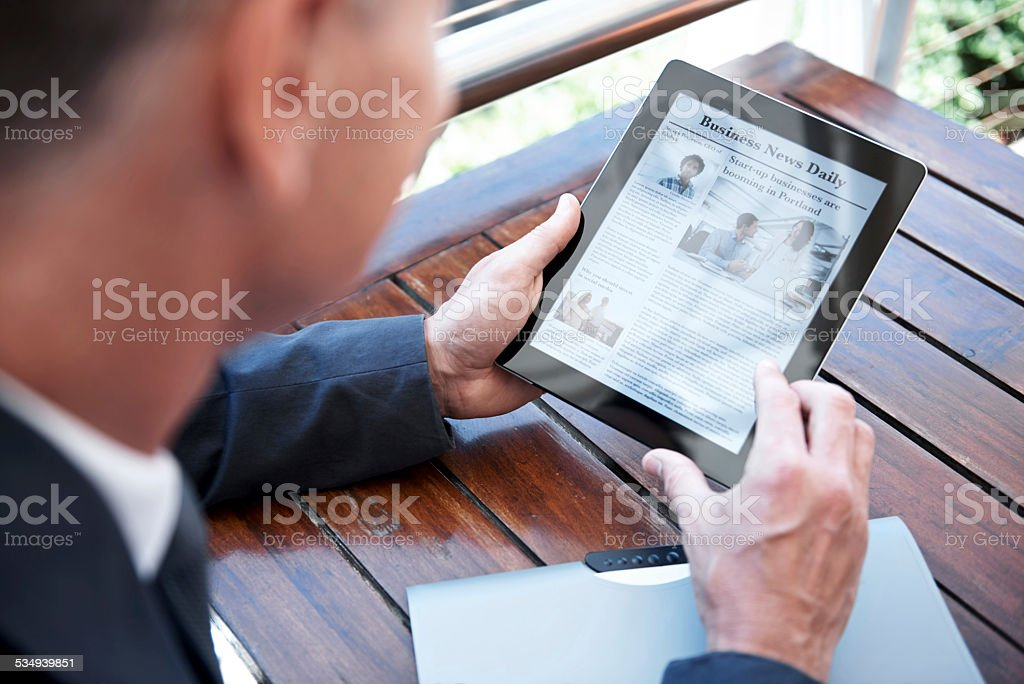 Checking up on the latest business news stock photo