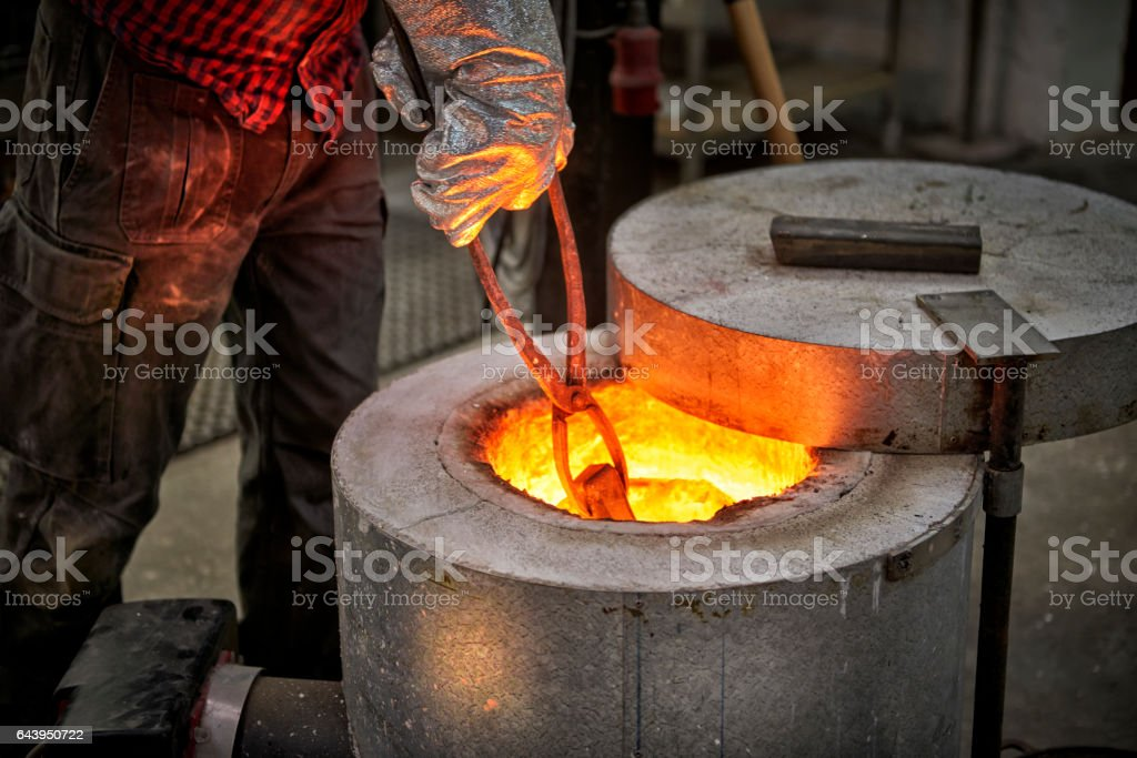 Checking up on the melted metal in oven stock photo
