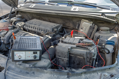istock checking voltage of car battery under the open hood of the car. lifestyle 1252278898