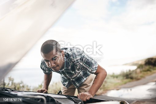 Cropped shot of a young man with his broken down car on the side of a road